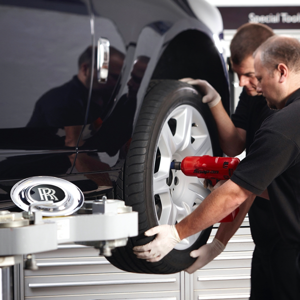 Rolls-Royce Motor Car master technicians working together to replace a wheel