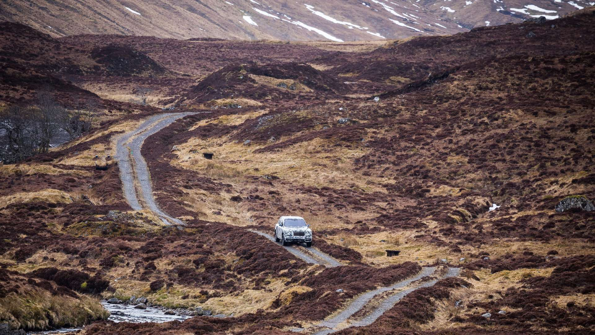A mountainous landscape with a dirt road running through it. The Rolls-Royce Cullinan drives down this terrain.