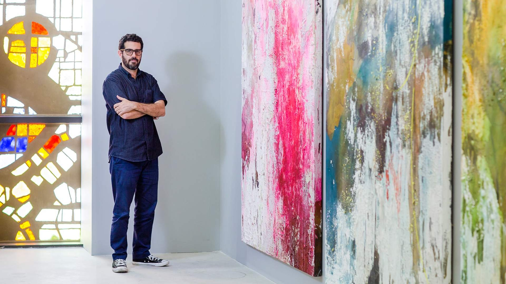 José Parlá standing in front of some of his art pieces. His work explores the connections between past and present by using colour and abstract calligraphy