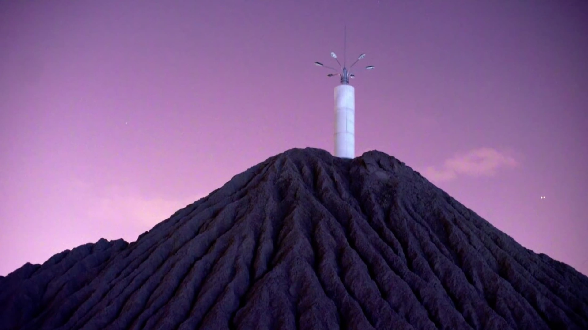 A still from Zhou Tao's Bienalle Arte 2017 entry, depicting a tower of lights against a purple hue night sky, atop a mountain