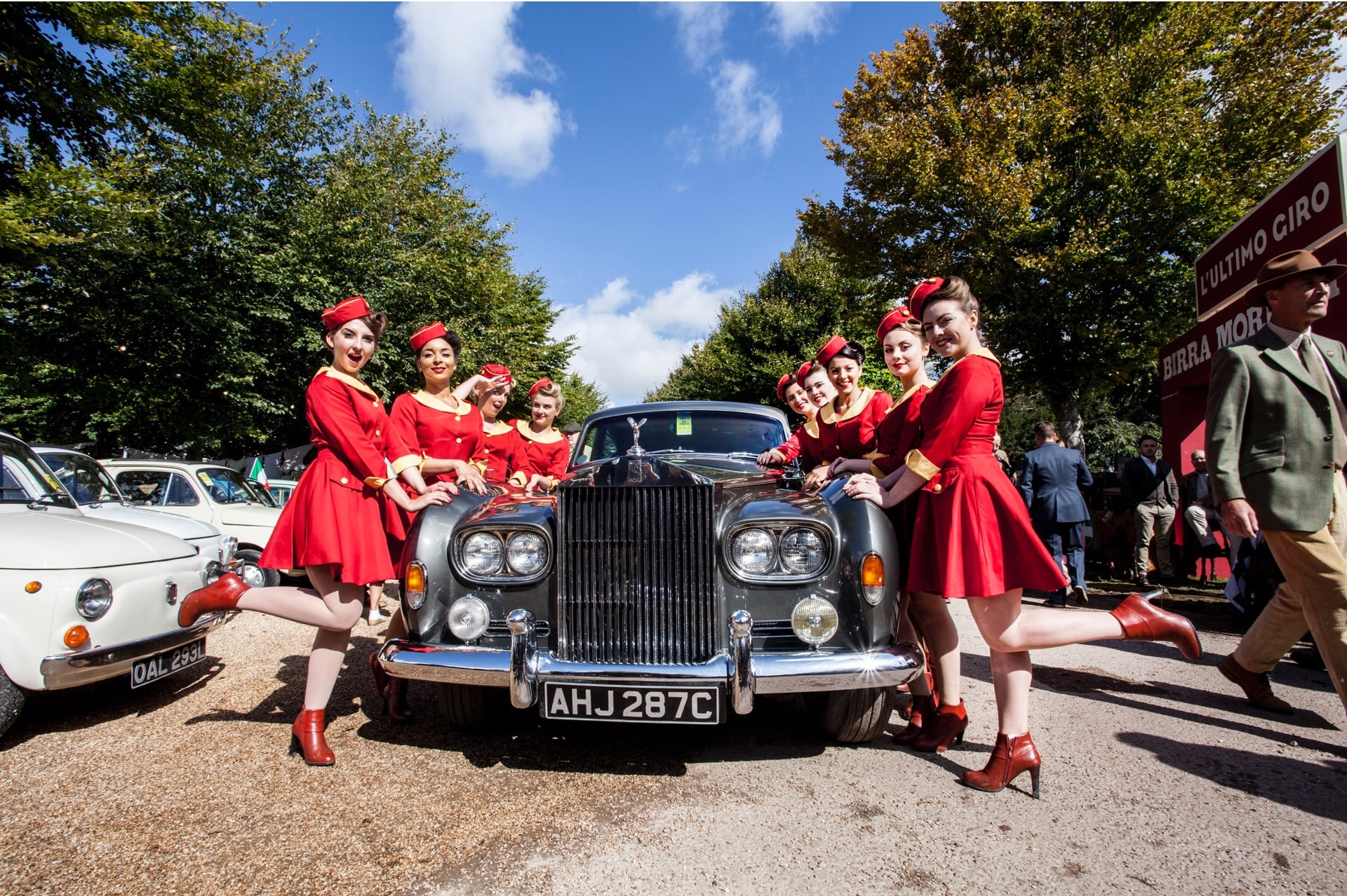 Enthusiasts clad in the fashion of bygone eras at the Rolls-Royce Goodwood Revival experience.