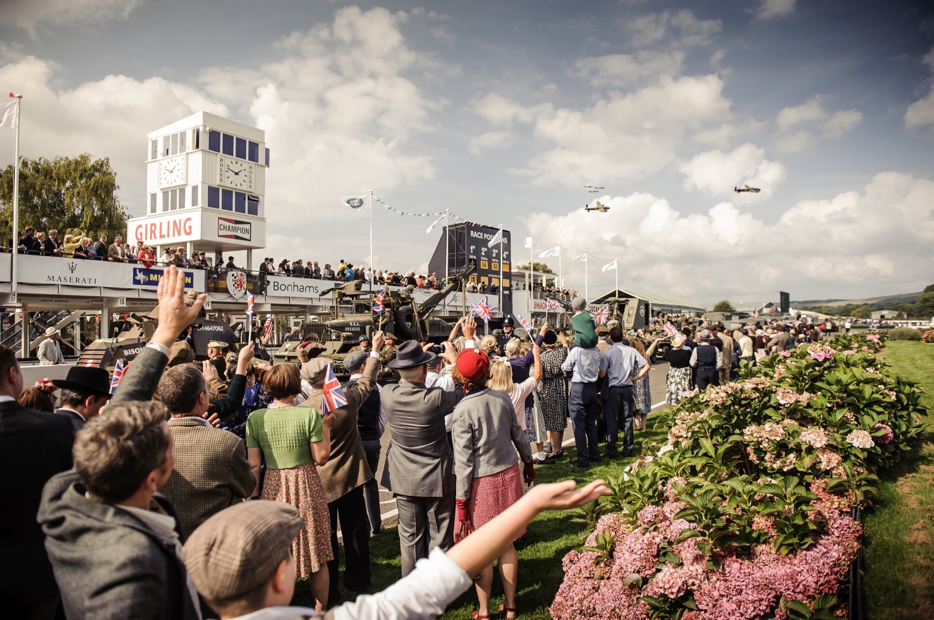 Spectators clad in the fashion of bygone eras at the Rolls-Royce Goodwood Revival experience.