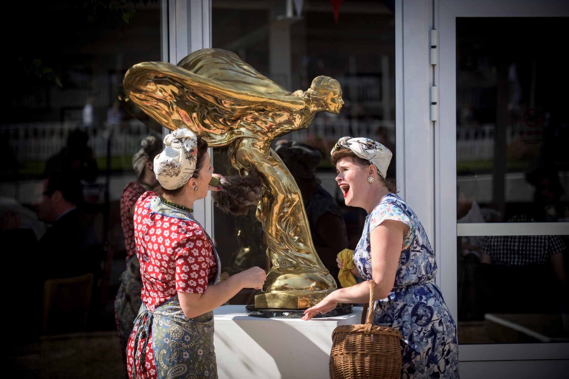Enthusiasts clad in the fashion of bygone eras stand with a giant gold Spirit of Ecstasy at the Rolls-Royce Goodwood Revival experience.