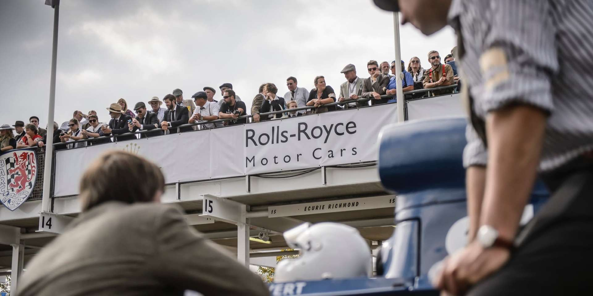 Crowd of spectators clad in the fashion of bygone eras at the Rolls-Royce Goodwood Revival experience.