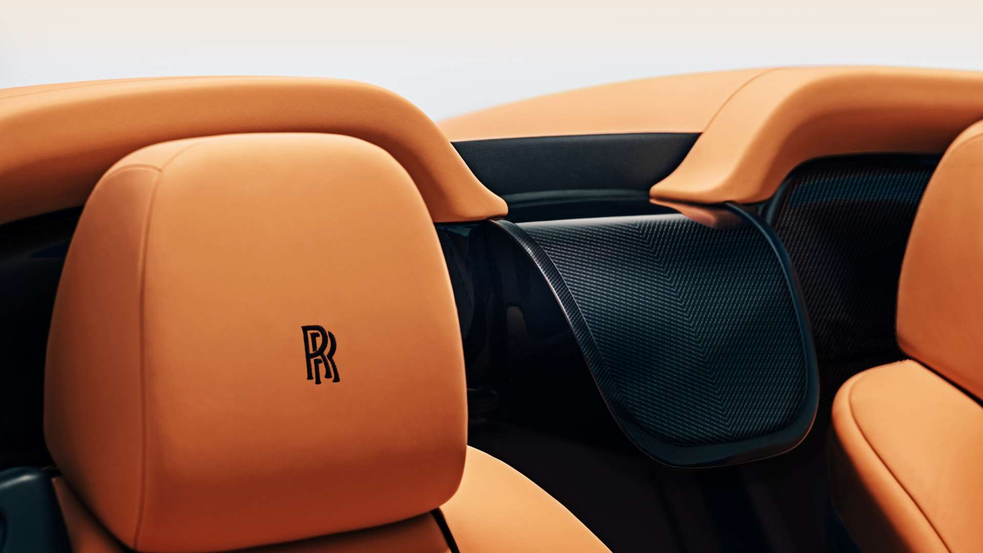 A close up of an orange leather headrest on a convertible Rolls-Royce Dawn