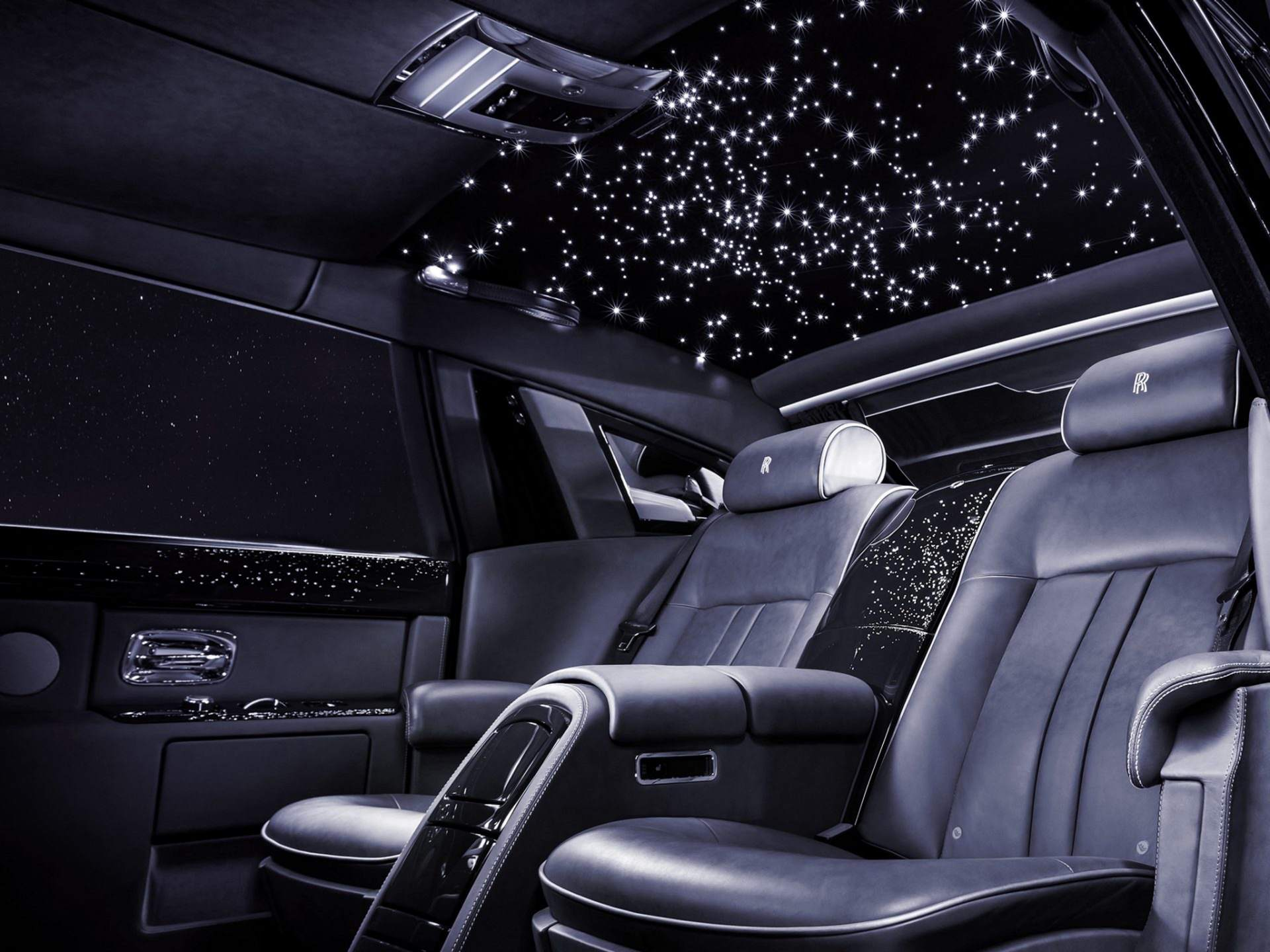 A fully black Rolls-Royce interior with the Starlight Headliner above the back passenger seats