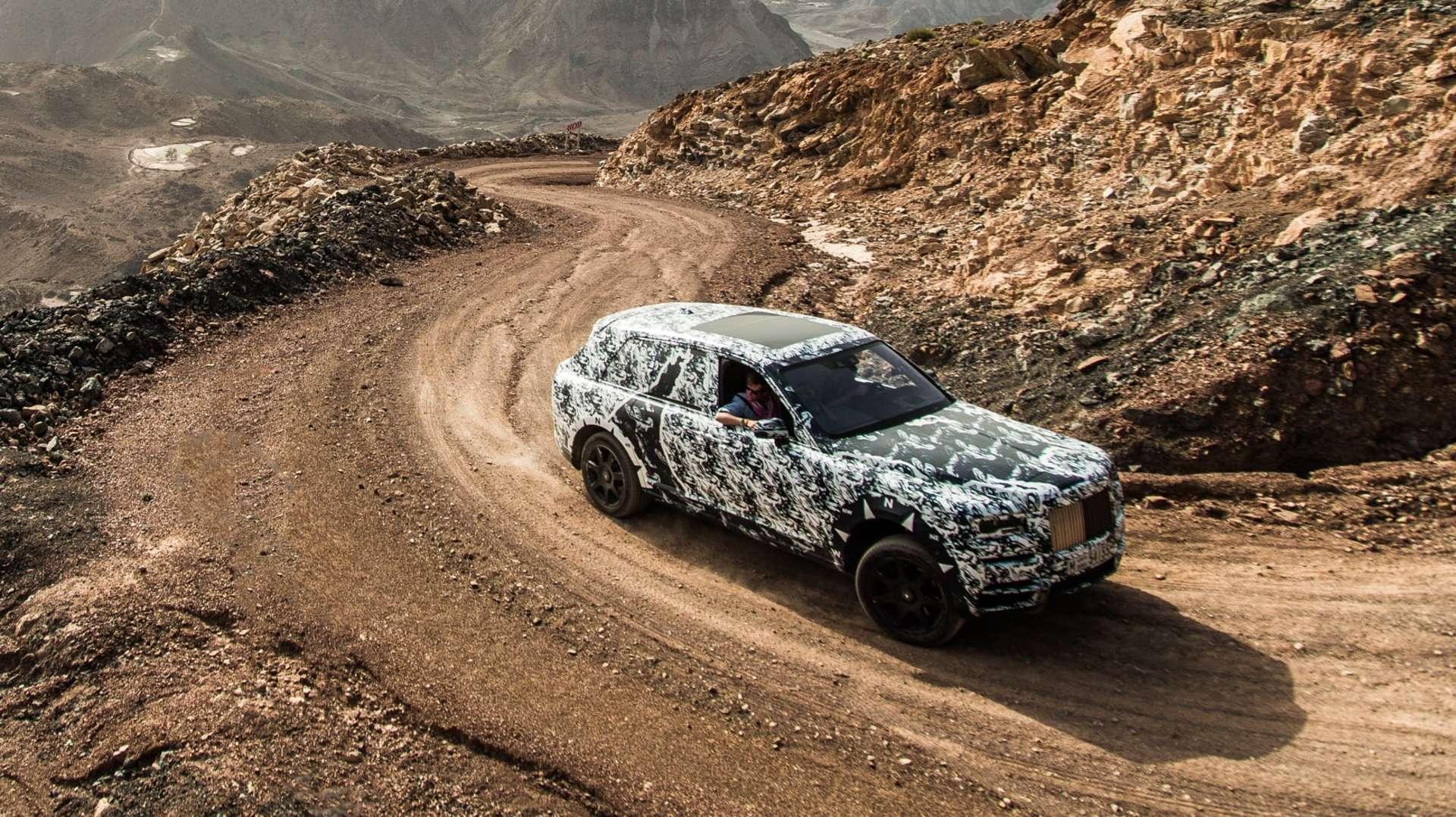 A Rolls-Royce Cullinan motor car driving through rocky terrain