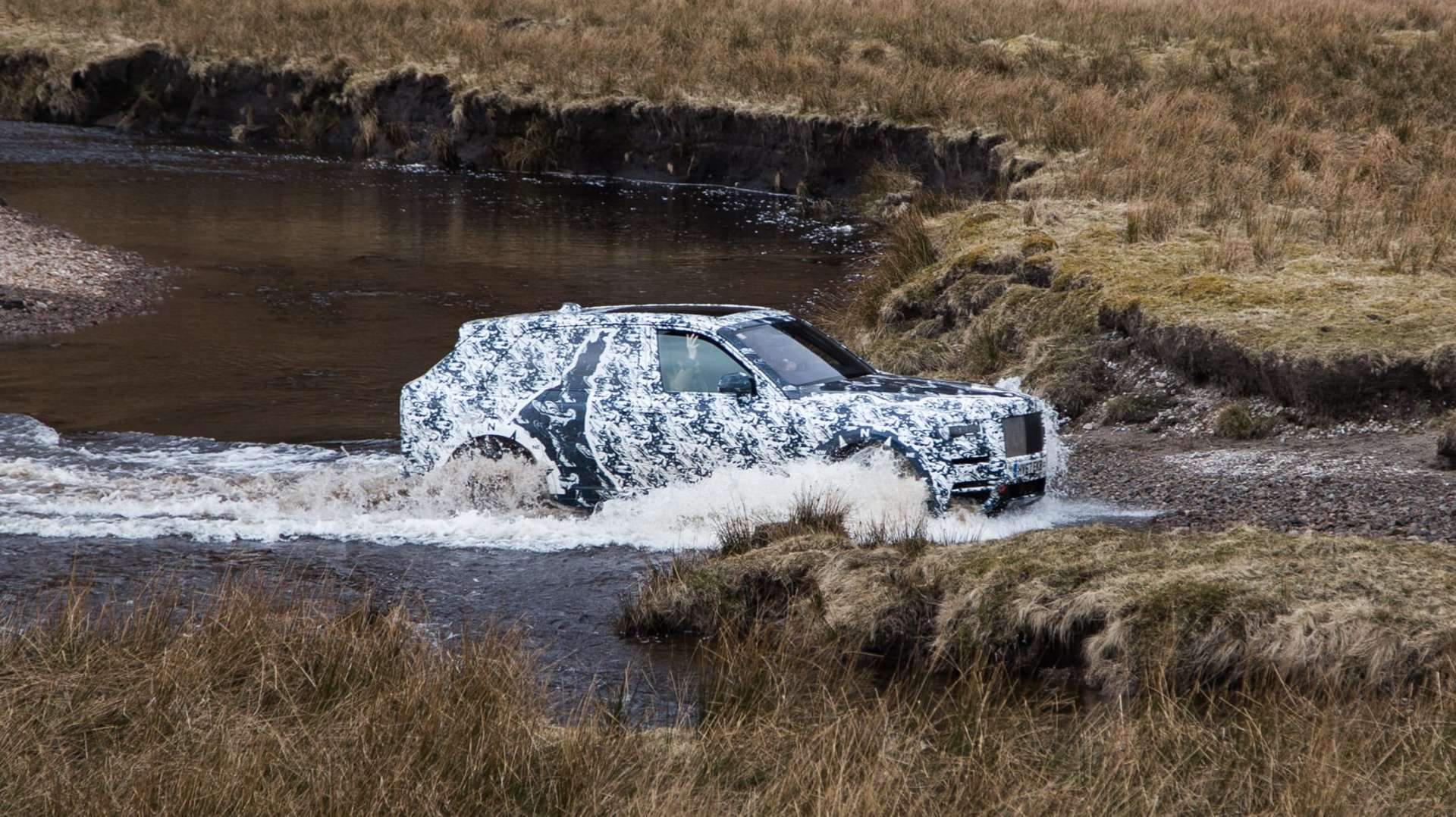 A Rolls-Royce Cullinan motor car driving through shallow water