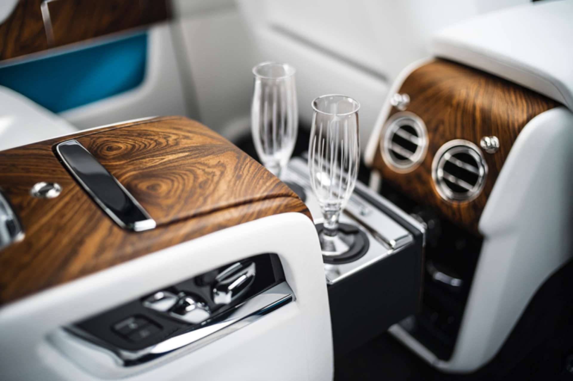 The interior of a Rolls-Royce Cullinan, featuring champagne glasses