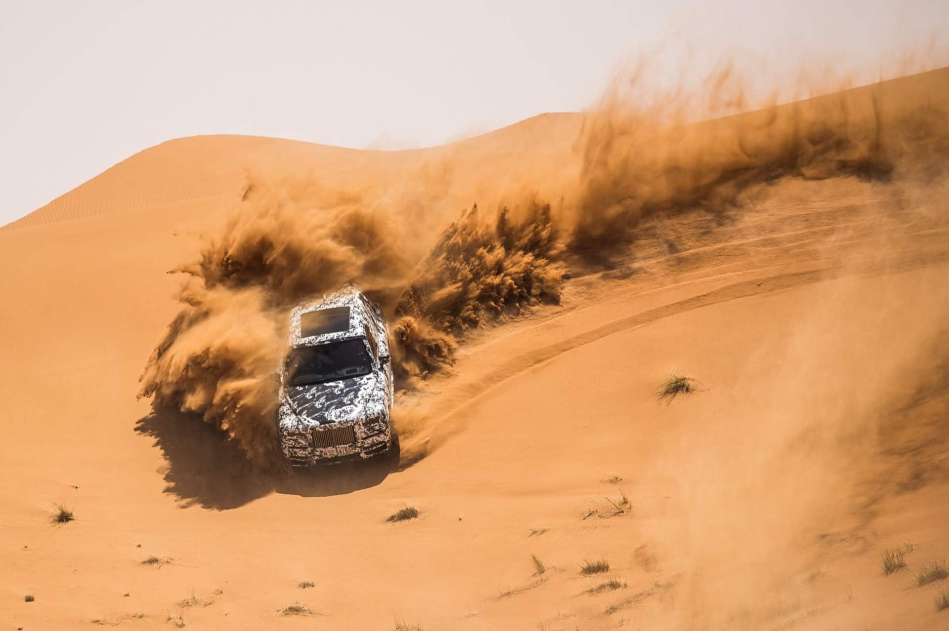 A Rolls-Royce Cullinan motor car drives through a desert