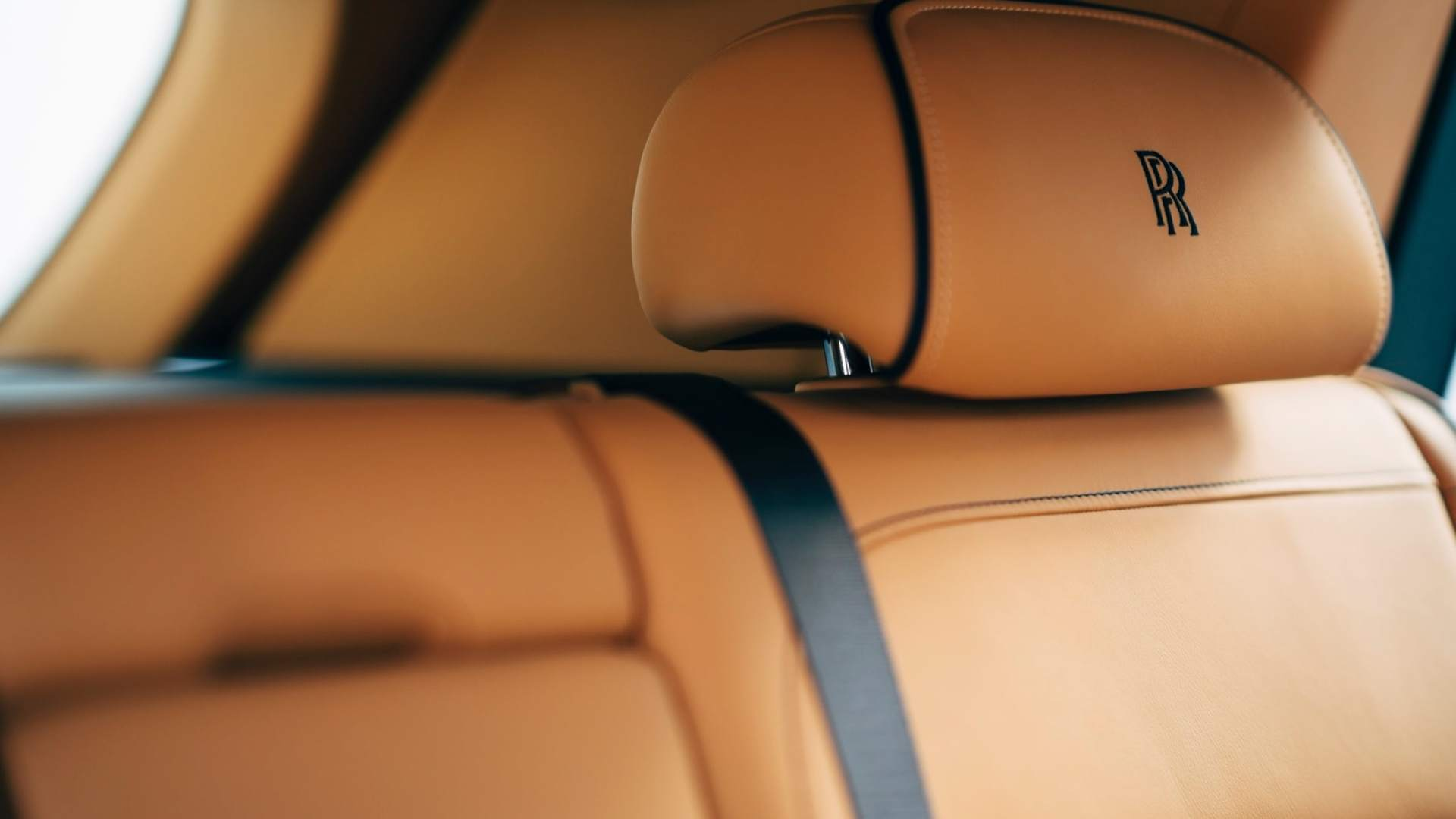 The monogrammed headrest of a Rolls-Royce Cullinan motor car