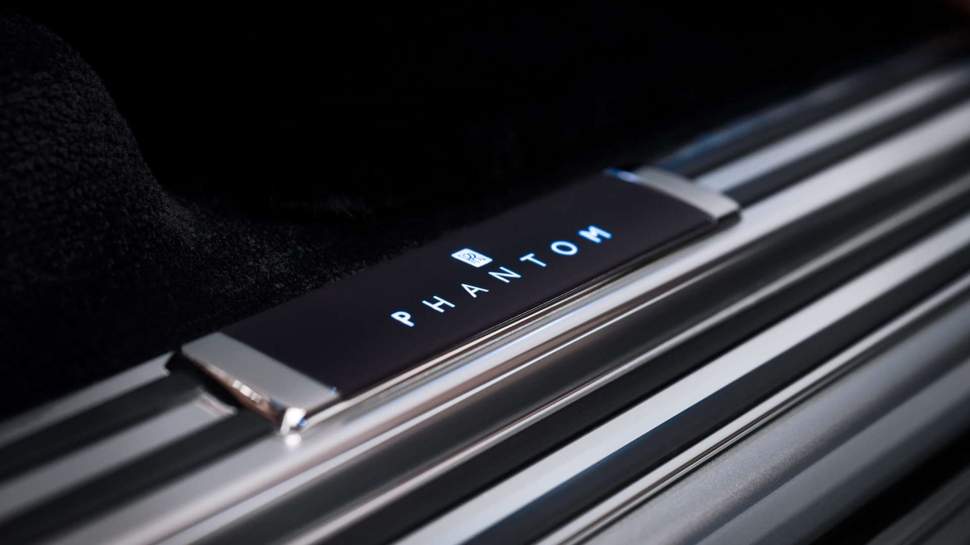 A close up of an illuminated tread plate on a Rolls-Royce Phantom Motor Car