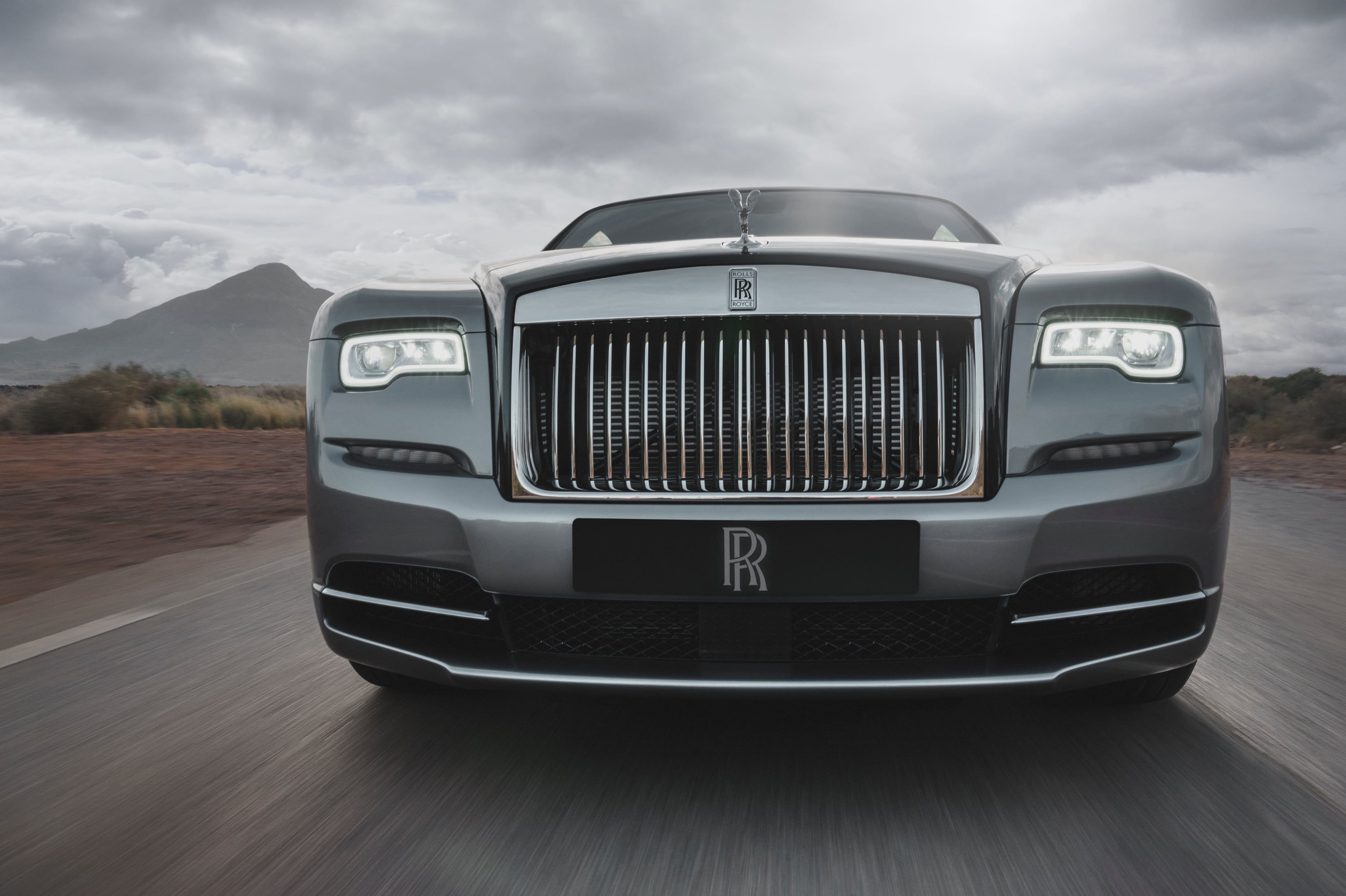 Rolls-Royce Wraith on the road, front symmetrical view of  lights and grille close up, with mountains in background