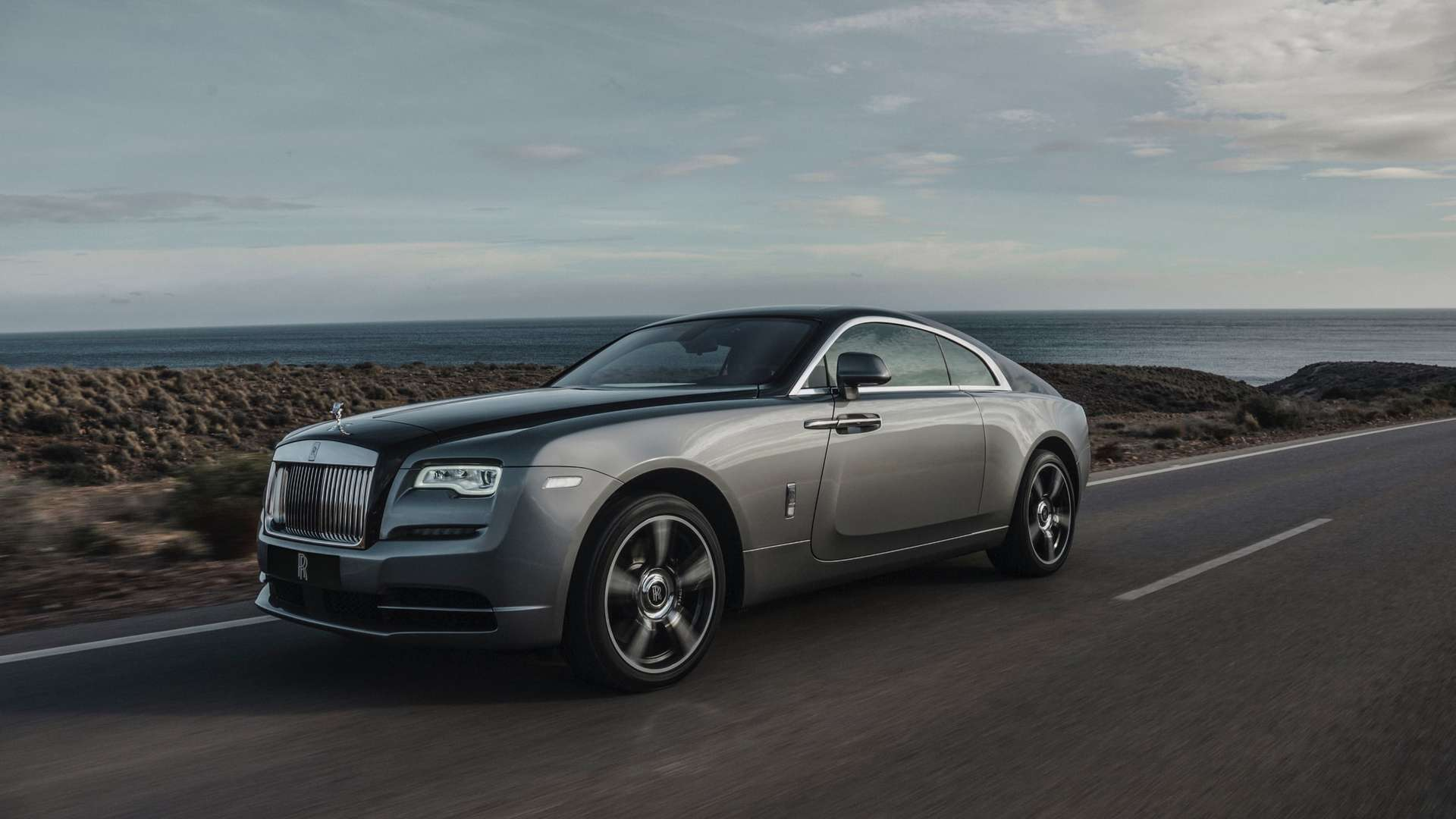 Rolls-Royce Wraith on the road, front side view, coastal path with sea view and cloudy sky
