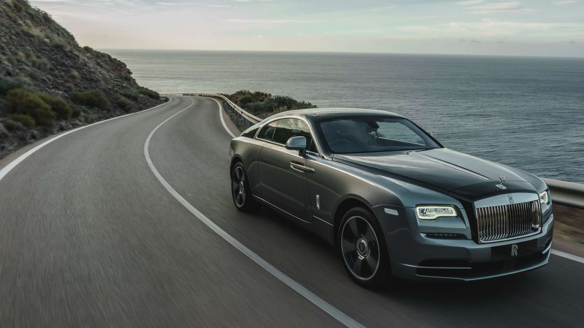 Rolls-Royce Wraith on the road, front side view, coastal path with sea view