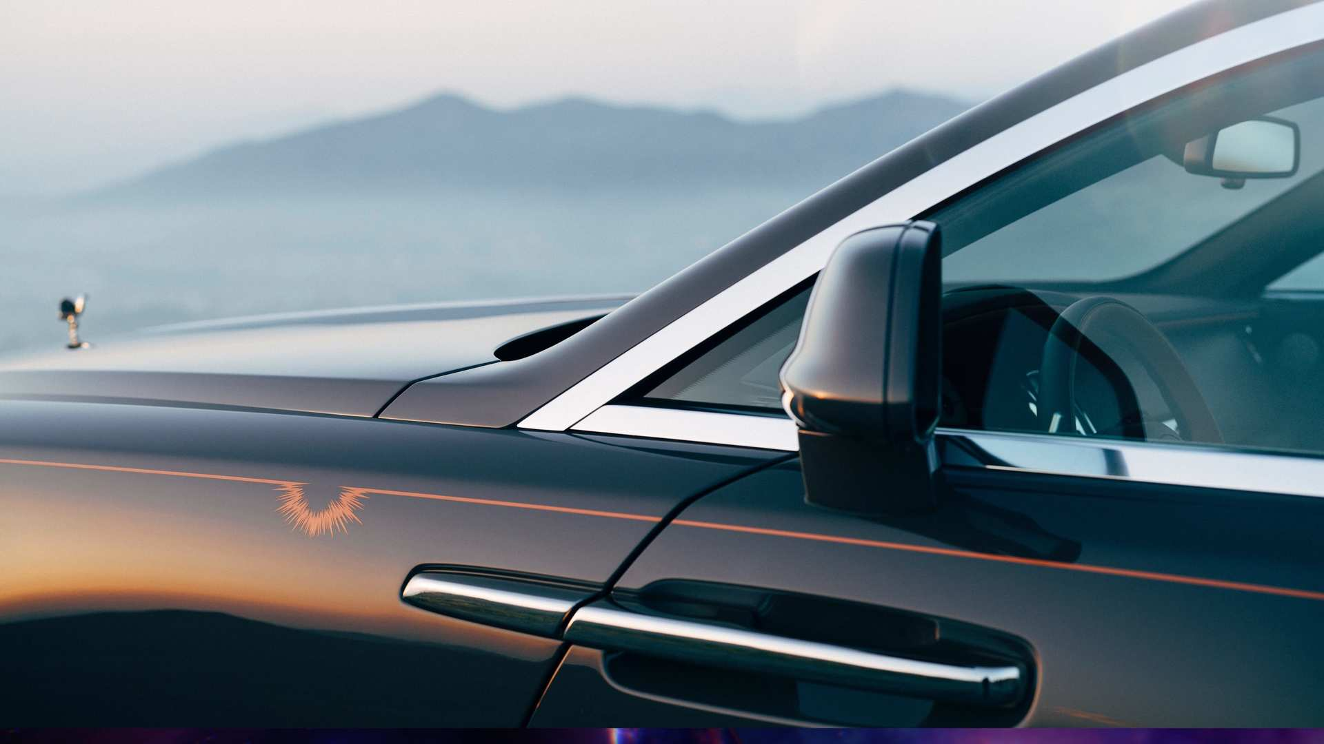 Rolls-Royce Wraith in detail side entry showing wing mirror driver side, reflection of red sunset on car door and faint mountains in background