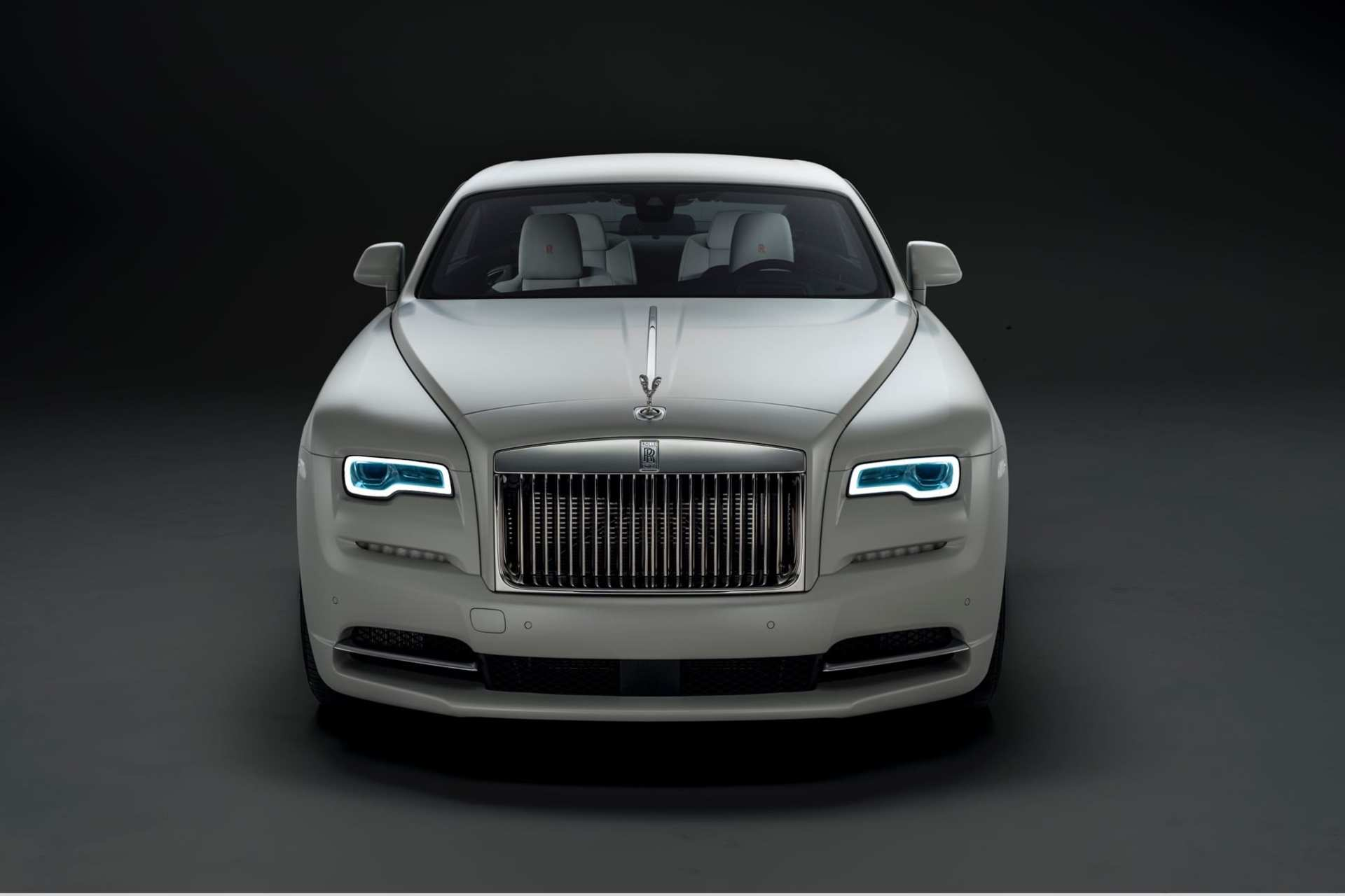 Rolls-Royce Wraith front angle view. Dark background, light car. Front headlights on