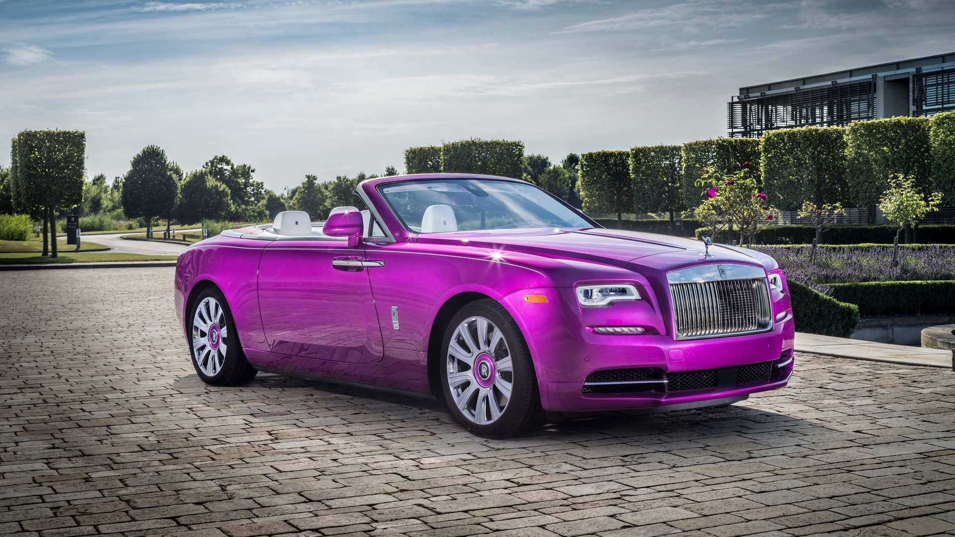 An electric fuchsia Rolls-Royce Dawn convertible is parked in front of sculptural hedges and trees in the parking lot of Goodwood, the Home of Rolls-Royce