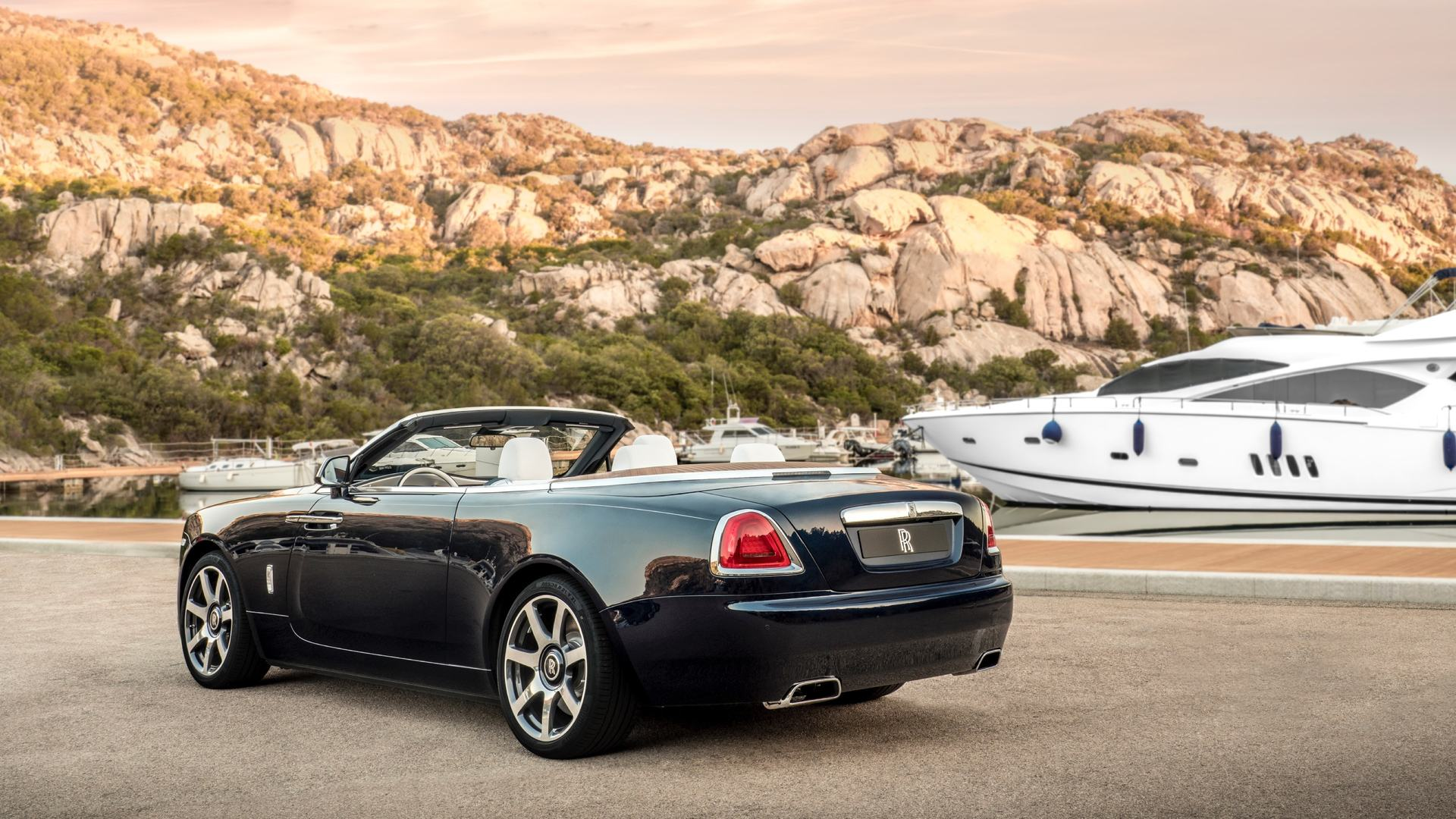 Rear view of Rolls-Royce Dawn Porto Cervo next to a boat