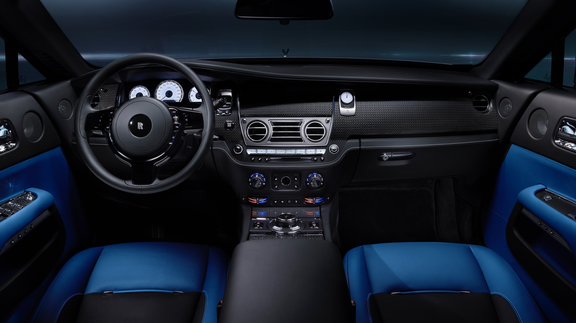The interior of a Rolls-Royce Black Badge Wraith showing the steering wheel and dashboard from the front passenger and drivers perspective.