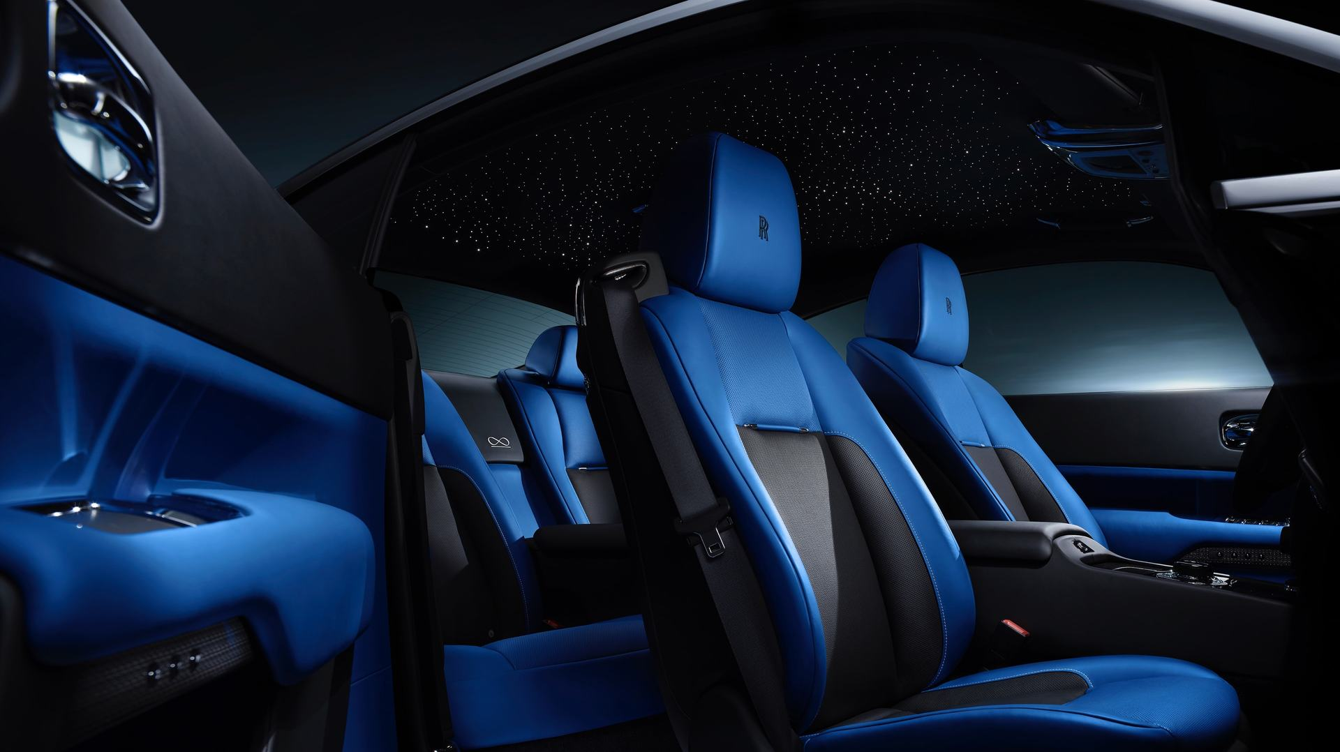 The blue seats and starlight headliner are shown in detail from the perspective of the drivers door being opened of a Rolls-Royce Black Badge Wraith.