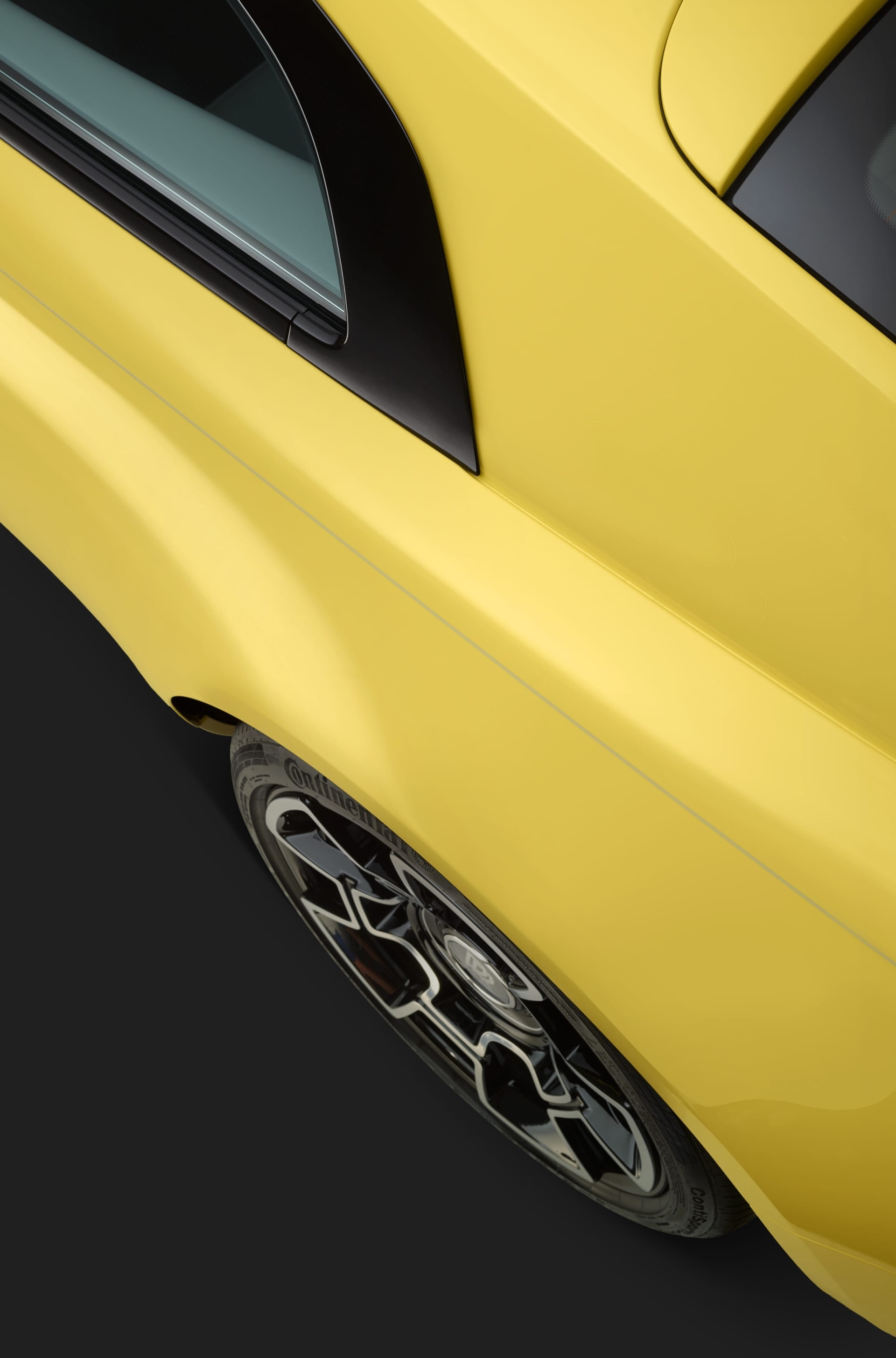 A zoomed in aerial elevated shot of the Rolls-Royce Semaphore Yellow Black Badge Wraith revealed at Pebble Beach.