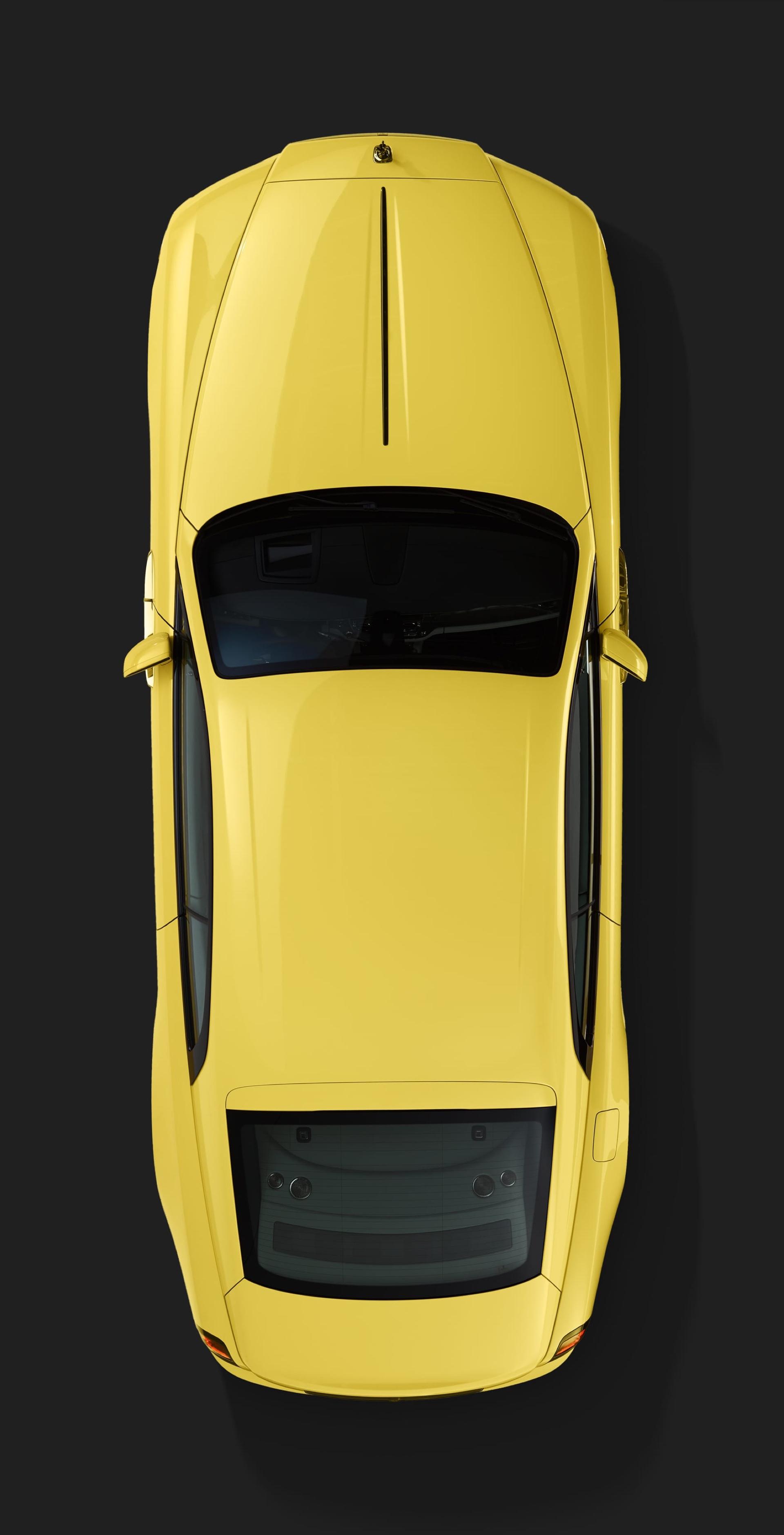 birds-eye shot of the Rolls-Royce Semaphore Yellow Black Badge Wraith revealed at Pebble Beach with the roof up.
