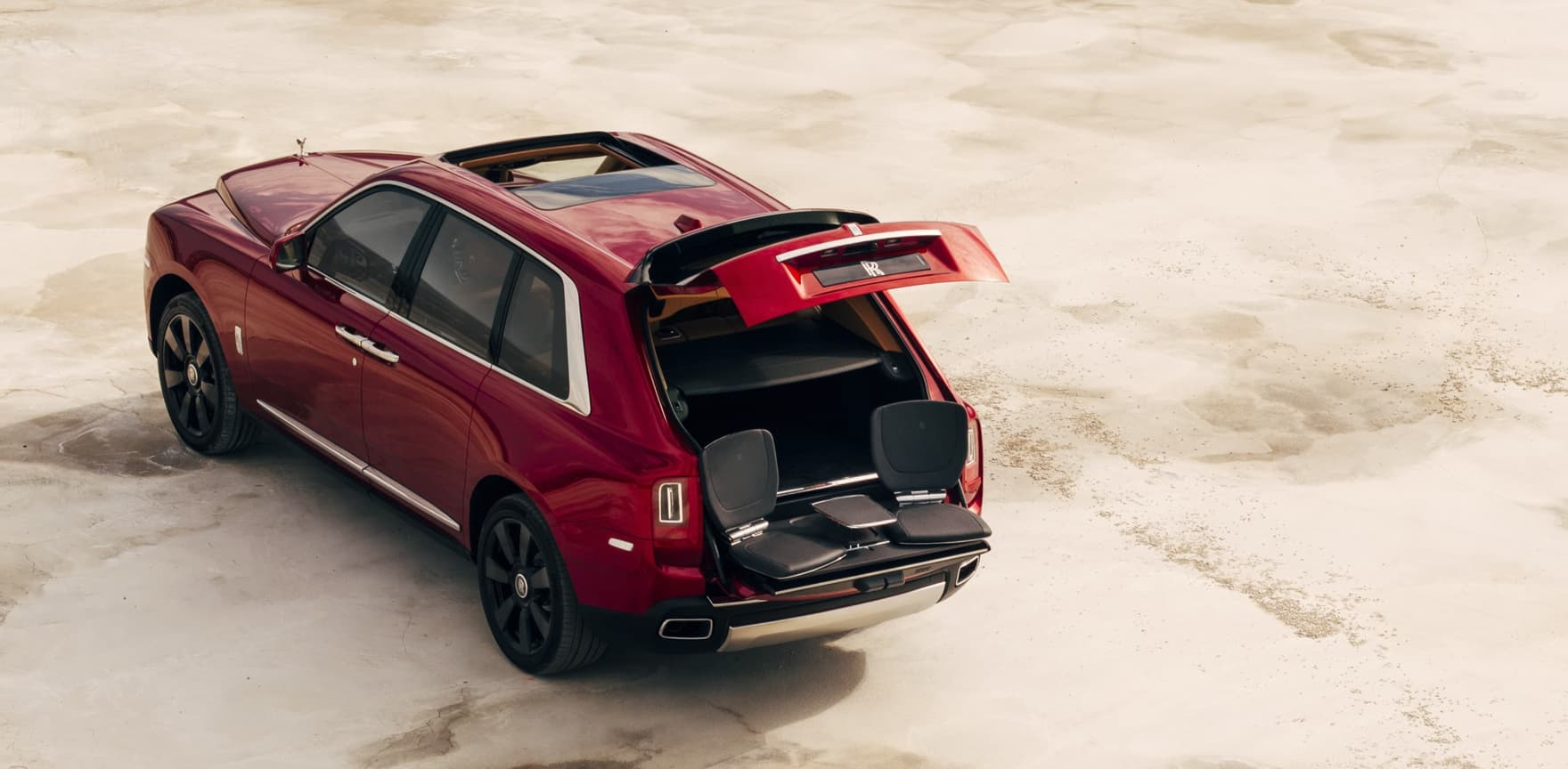Aerial rear view of stationary Rolls-Royce Cullinan motor car with rear door open revealing the bespoke Cullinan Viewing Suite