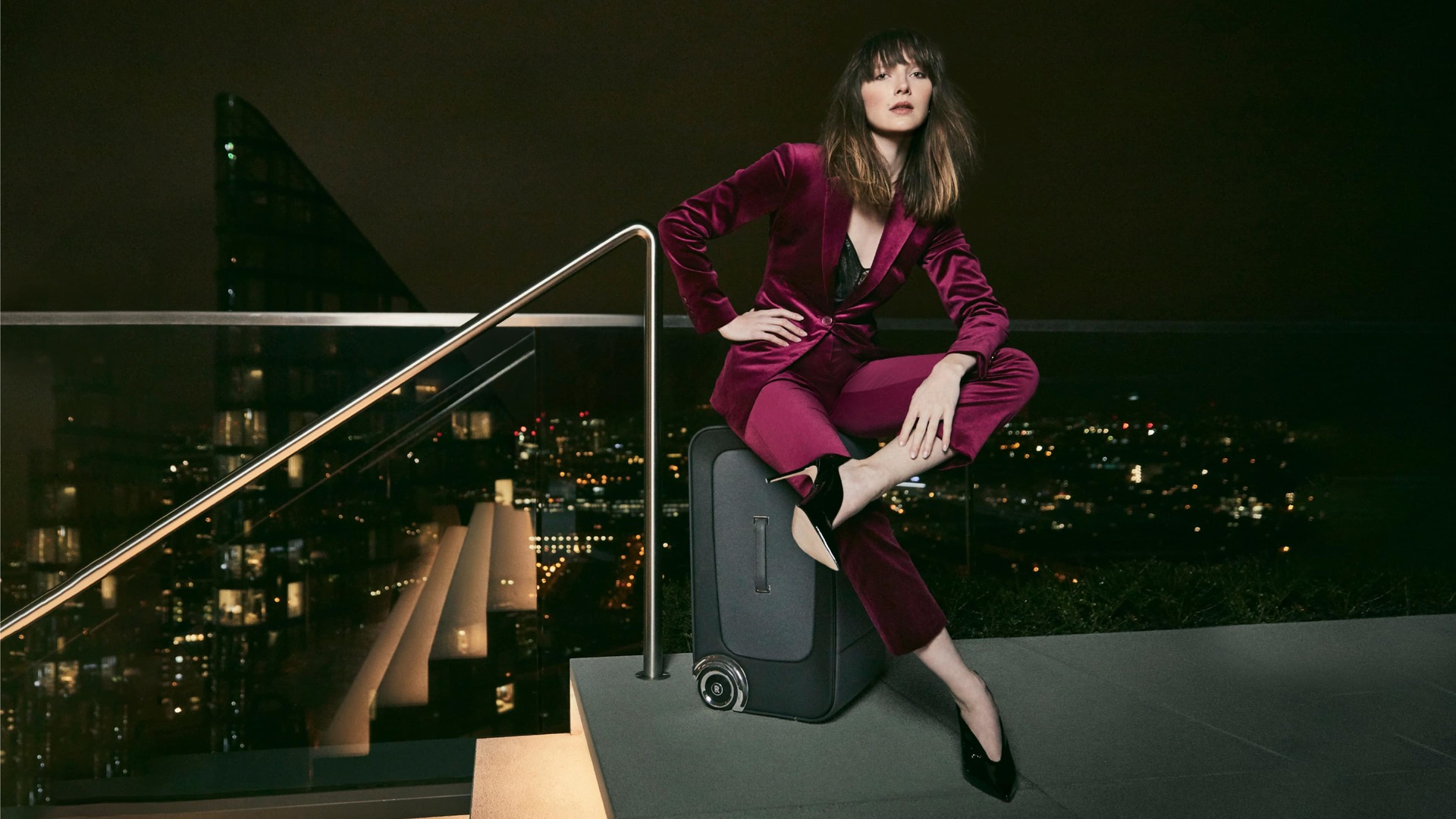 Woman sits upon Grand Tourer from Rolls-Royce Kinetic Luggage collection with night time city views in background