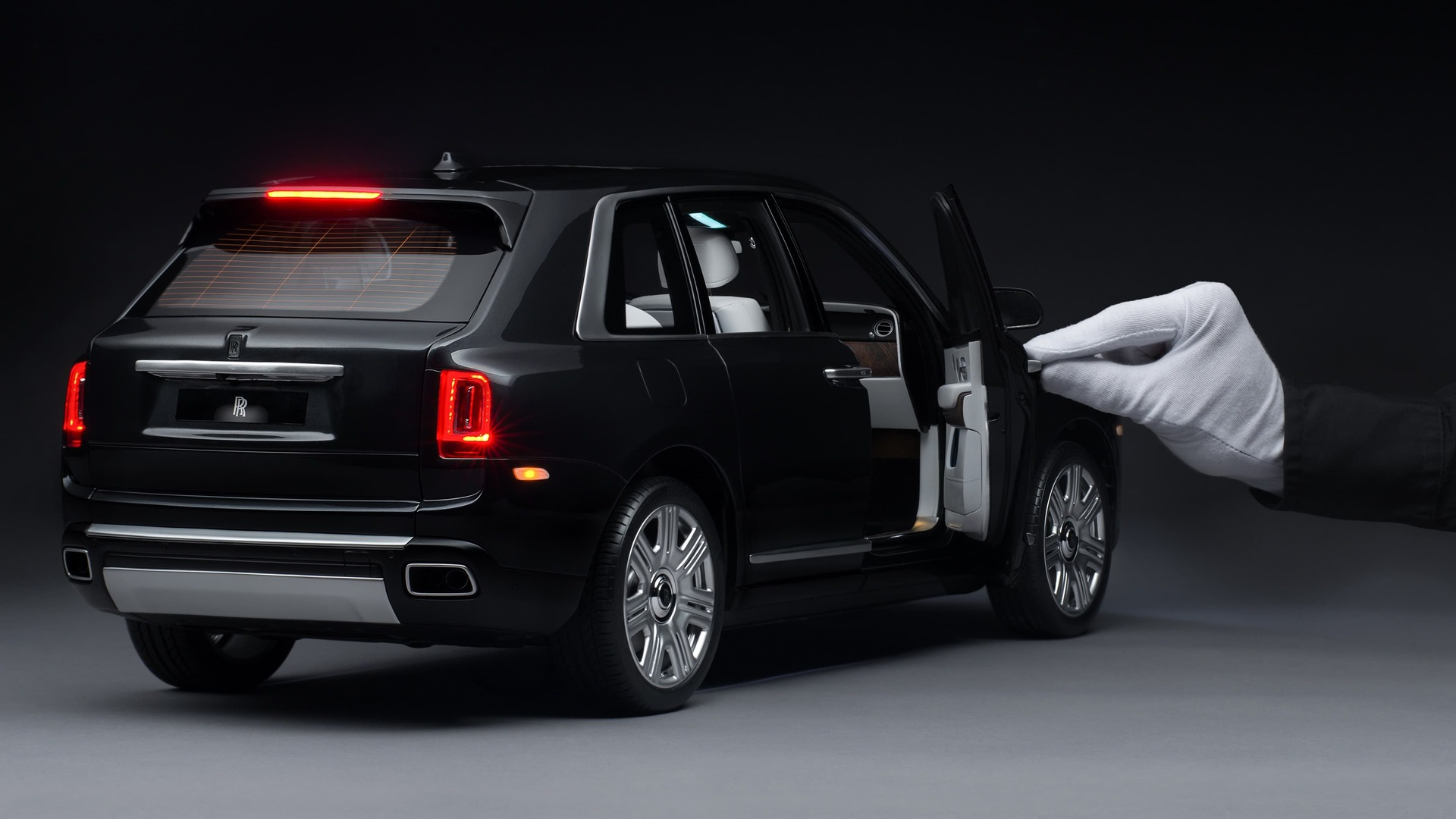 1:8 scale model of the Rolls-Royce Cullinan motor car with hand holding door open