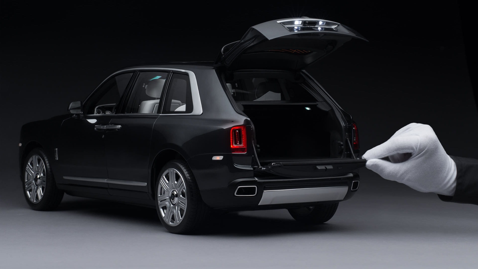 1:8 scale model of the Rolls-Royce Cullinan motor car with hand opening the trunk