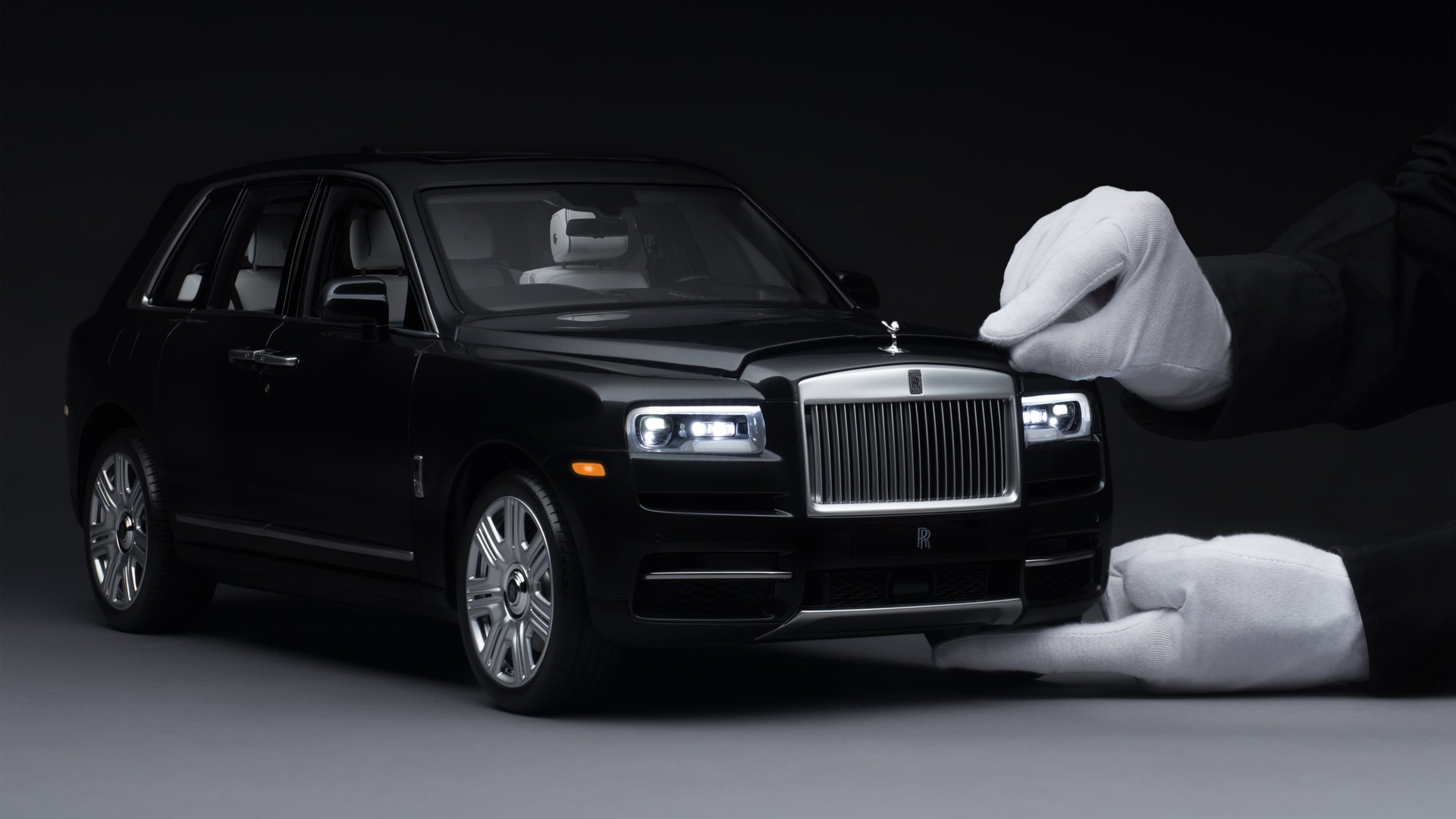 1:8 scale model of the Rolls-Royce Cullinan motor car with hand opening the bonnet