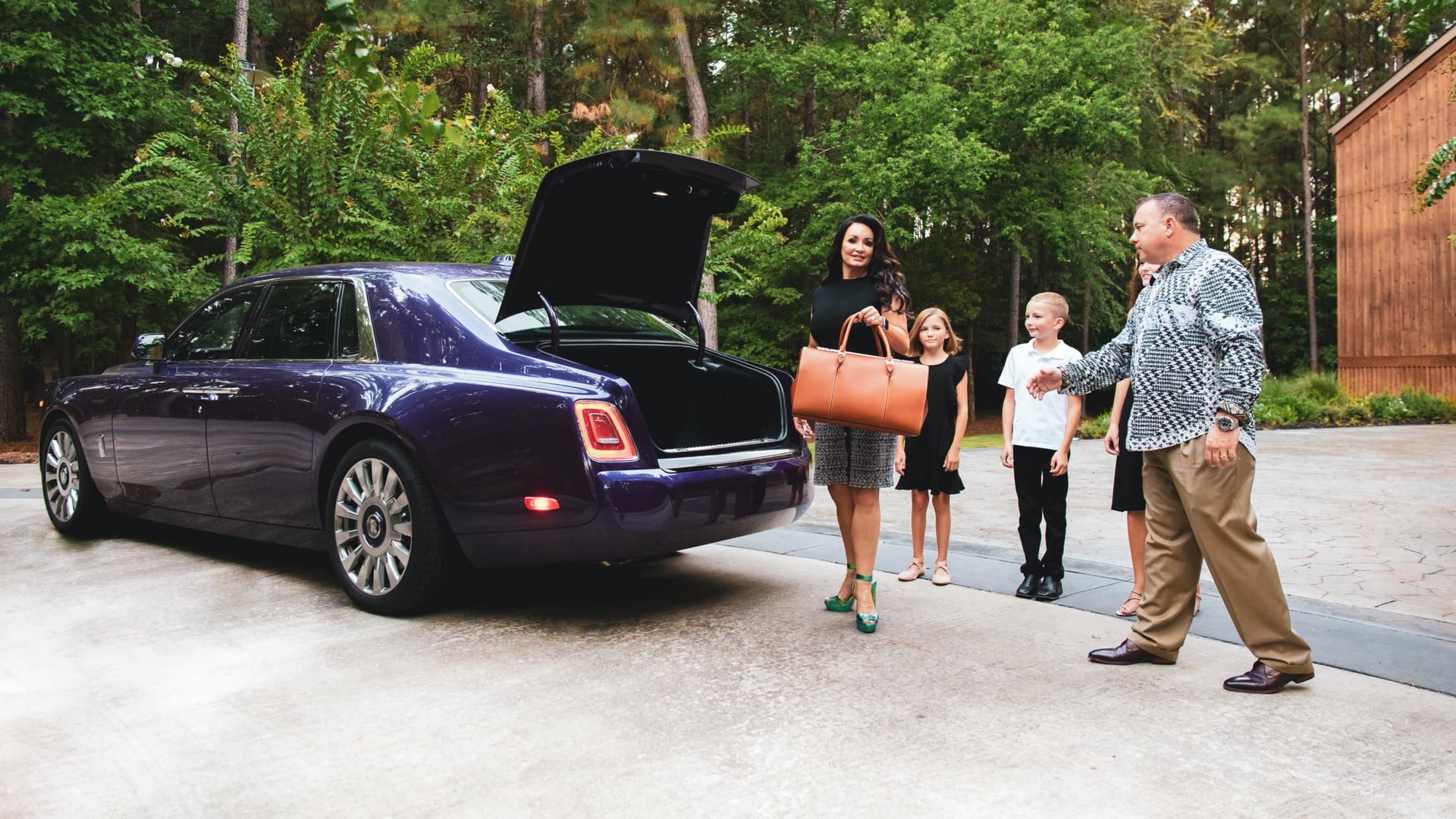Colleen Ellison and her family standing in front of her purple Rolls-Royce Phantom with the rear boot open, with Colleen holding a leather bag getting ready to put it inside the Phantom