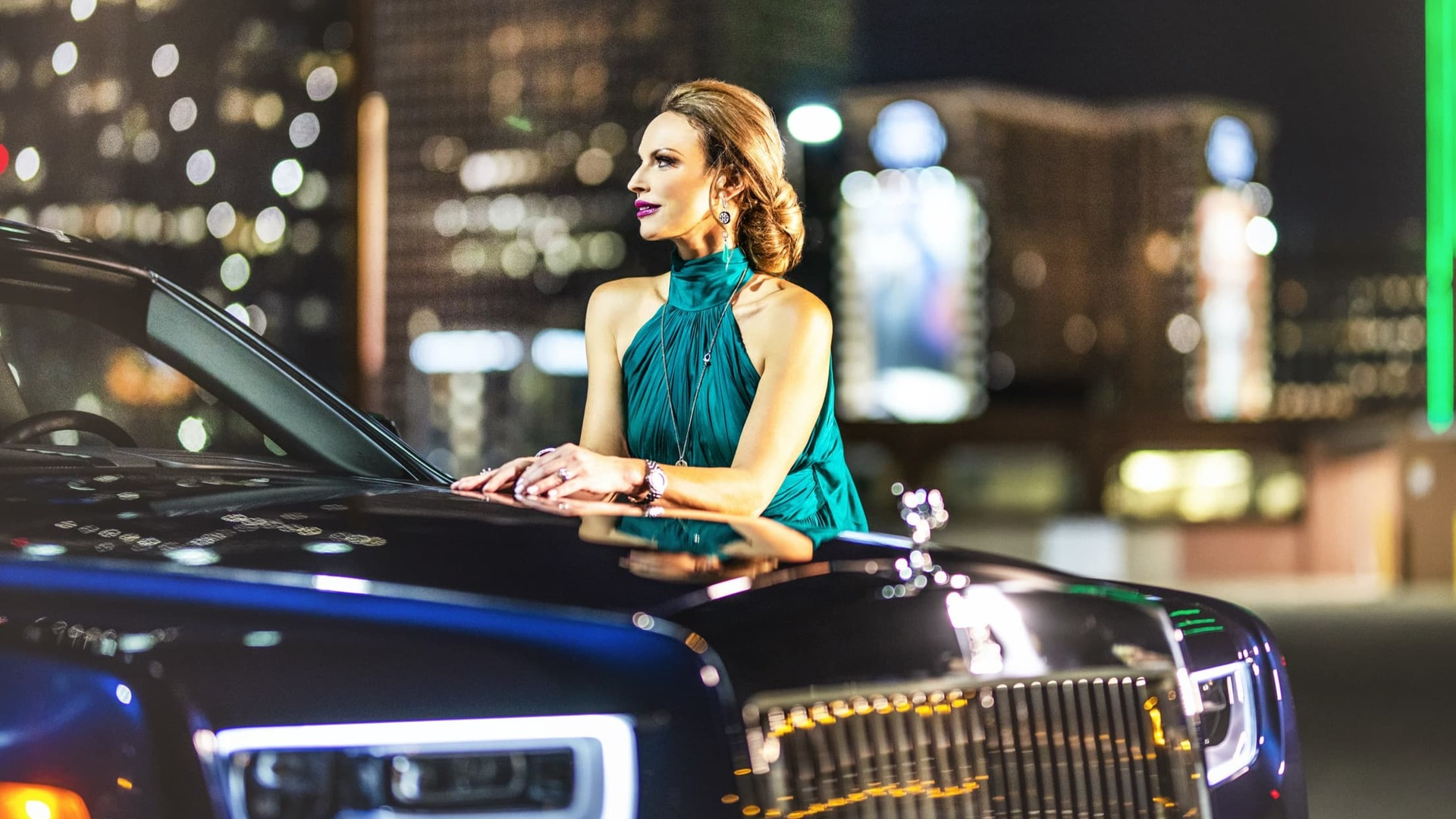 a night shot of Melissa Muller leaning against her dark blue Rolls-Royce Phantom with a cityscape in the background