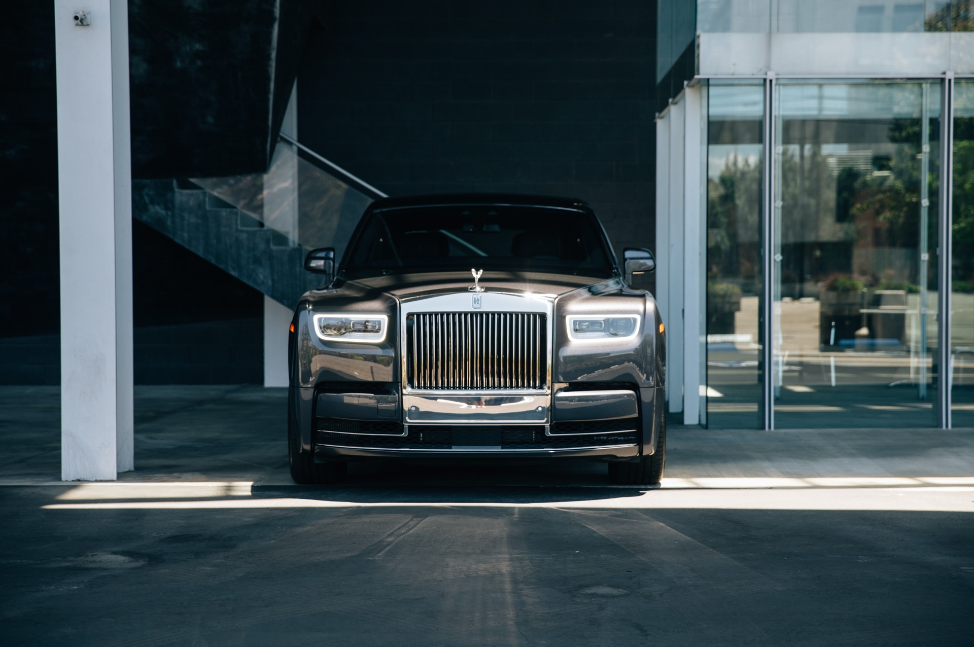 A front-on shot of the Rolls-Royce Phantom with bright sunlight reflecting against the Pantheon Grille and headlights