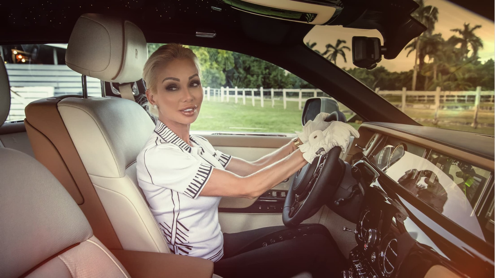 A shot of Sandra Fiorenza behind the wheel of her Rolls-Royce Phantom, holding the steering wheel with white leather driving gloves whilst looking towards the passenger seat