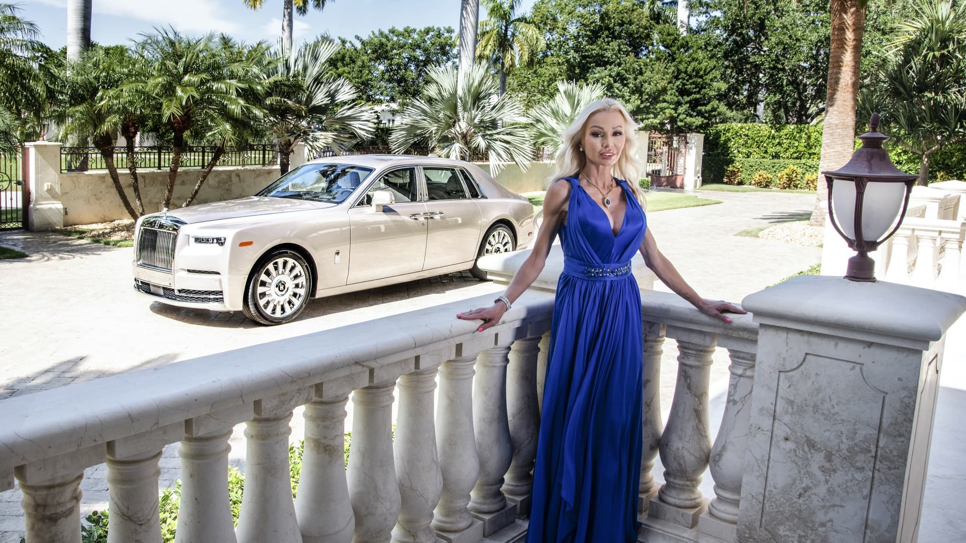 Sandra Fiorenza standing against a pillared porch wall in a long dark blue dress with her silver Rolls-Royce Phantom in the background