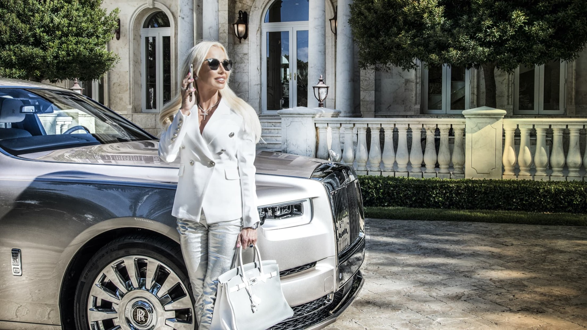 A shot of Sandra Fiorenza holding a white bag leaning against the front-right hand side of her silver Rolls-Royce Phantom